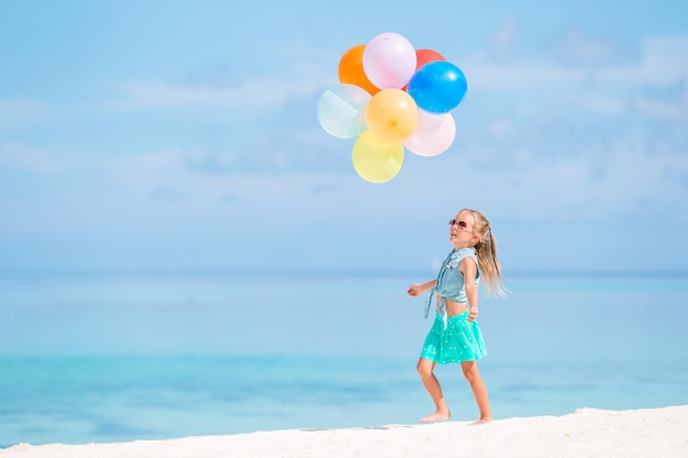 Entzückendes kleines mädchen, das mit luftballons am strand spielt