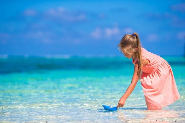 Entzückendes kleines mädchen, das mit origamiboot im türkismeer spielt