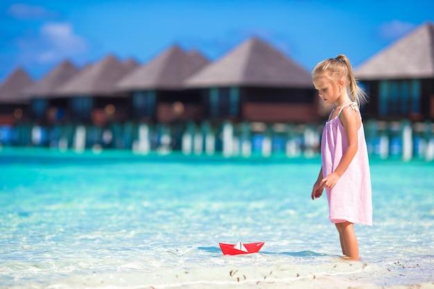 Entzückendes kleines mädchen, das mit papierboot im türkismeer spielt