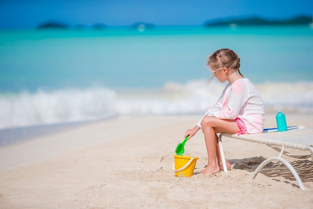 Entzückendes kleines mädchen, das mit spielwaren auf strandferien spielt. kind spielen mit sand