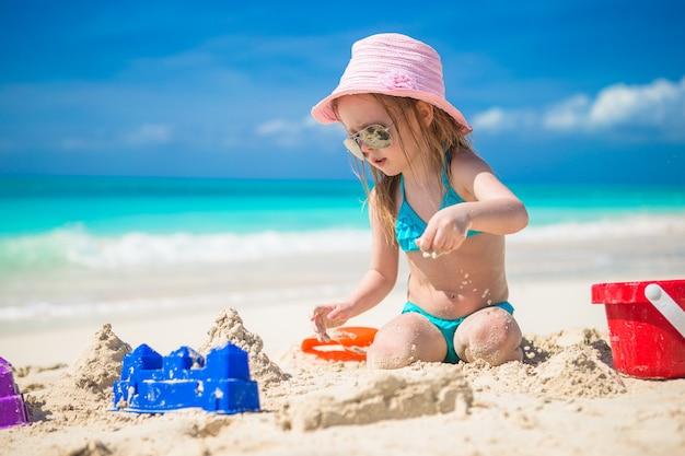 Entzückendes kleines mädchen, das mit spielwaren auf strandferien spielt