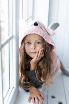 Entzückendes kleines mädchen, das rosa pullover trägt