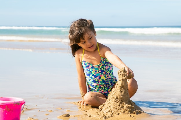 Entzückendes kleines mädchen, das sandburg am strand baut, auf nassem sand sitzt und urlaub am meer genießt