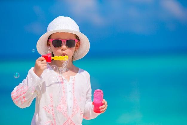 Entzückendes kleines mädchen, das seifenblasen während der sommerferien macht