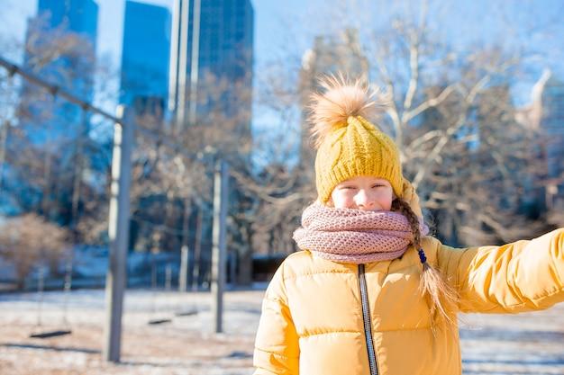 Entzückendes kleines mädchen, das selfie foto im central park in new york city macht