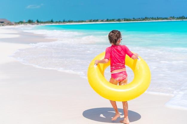Entzückendes kleines mädchen, das spaß auf dem strand hat