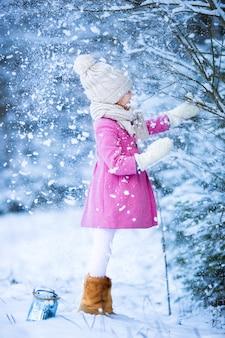 Entzückendes kleines mädchen, das spaß im schnee auf weihnachten am winterwald draußen hat
