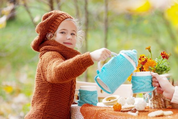 Entzückendes kleines mädchen, das tee im herbstpark trinkt