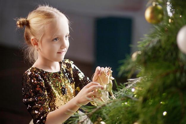Entzückendes kleines mädchen, das zu hause weihnachtsbaum verziert. weihnachts- und neujahrsfeier.