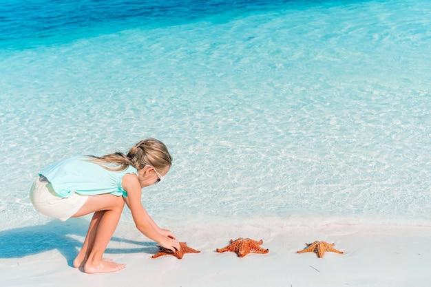 Entzückendes kleines mädchen haben spaß am tropischen strand während des urlaubs