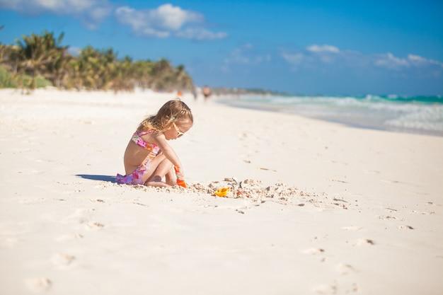Entzückendes kleines mädchen im badeanzug, der am tropischen karibischen strand spielt