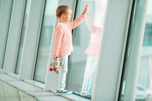 Entzückendes kleines mädchen im flughafen mit ihrem gepäck, das auf einstieg wartet