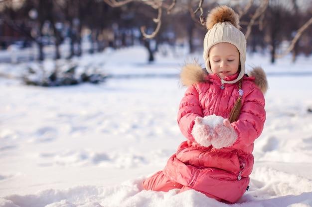 Entzückendes kleines mädchen im freien im park am kalten wintertag
