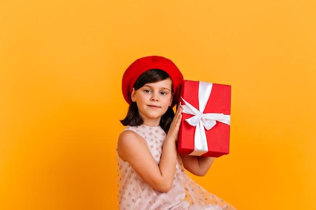 Entzückendes kleines mädchen im kleid, das geburtstagsgeschenk hält. kind erraten, was in geschenk.