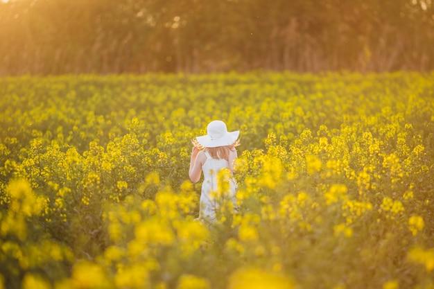 Entzückendes kleines mädchen im weißen kleid und im hut läuft auf frühlingsfeld der gelben blumen