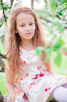 Entzückendes kleines mädchen in blühendem apfelbaumgarten am frühlingstag