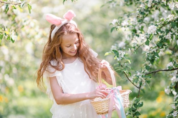 Entzückendes kleines mädchen in blühendem apfelgarten am schönen frühlingstag