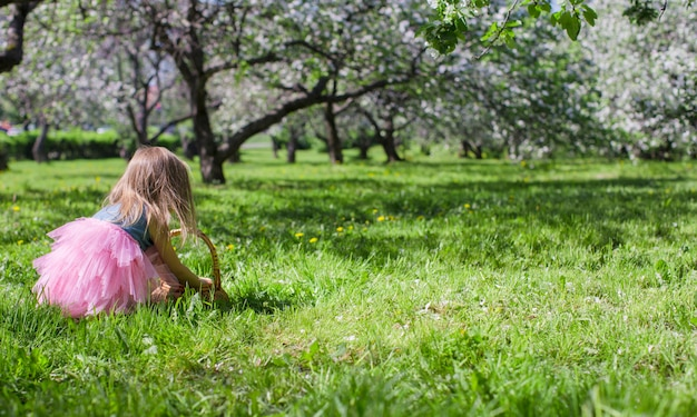 Entzückendes kleines mädchen in blühendem apfelgarten