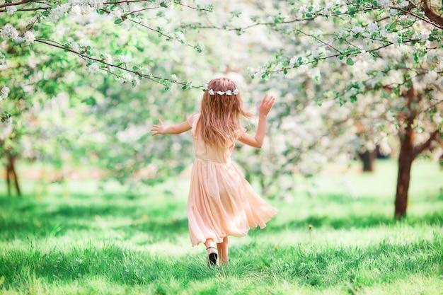 Entzückendes kleines mädchen in blühendem kirschbaumgarten draußen