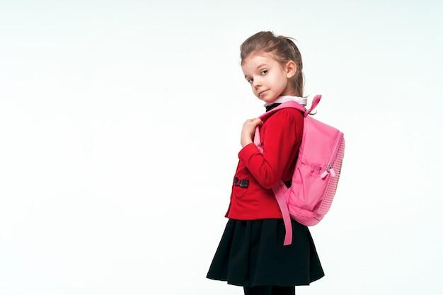 Entzückendes kleines mädchen in der roten schuljacke, im schwarzen kleid, an den trägern eines rucksacks und lächelnd und in die kamera schauend, auf weißem raum posierend. isolieren