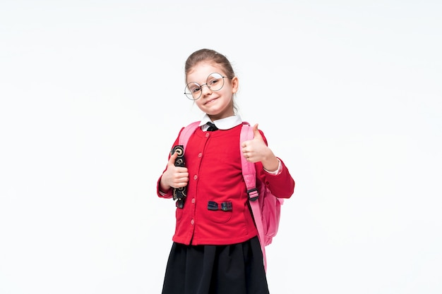 Entzückendes kleines mädchen in der roten schuljacke, im schwarzen kleid, in der abgerundeten brille und im rucksack, die daumen zeigen, während sie auf weißem raum aufwerfen. isolieren