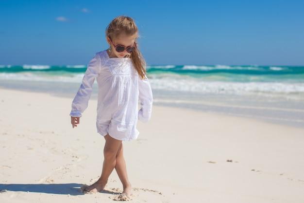 Entzückendes kleines mädchen in der schönen kleidung, die am tropischen strand tanzt