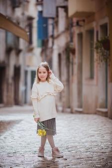 Entzückendes kleines mädchen in der tendenz kleidet stellung in der alten stadt am sonnigen frühlingstag mit gelben blumen