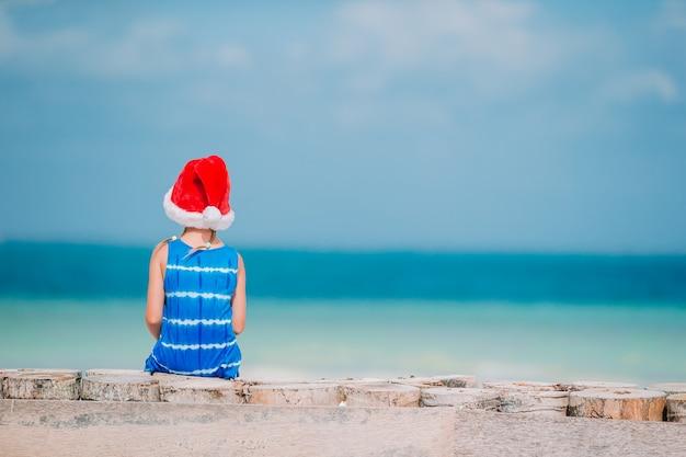 Entzückendes kleines mädchen in der weihnachtsmütze am tropischen strand