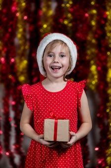 Entzückendes kleines mädchen in der weihnachtsmütze hält neujahrsgeschenk und lächelt.