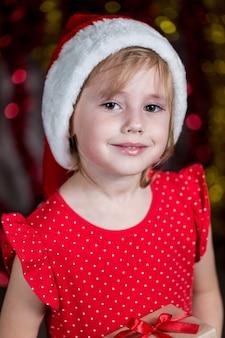 Entzückendes kleines mädchen in der weihnachtsmütze lächelt.