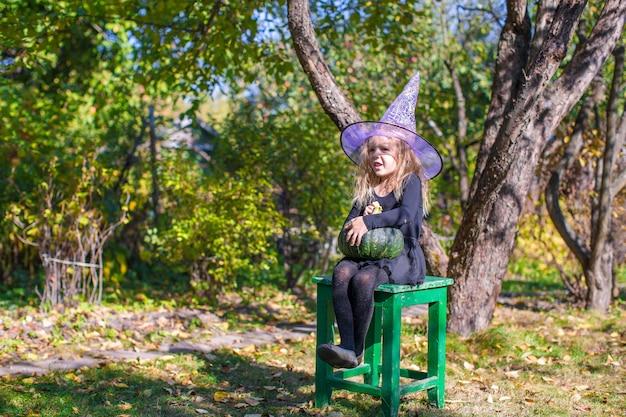 Entzückendes kleines mädchen in halloween, welches kostüm spaß draußen hat