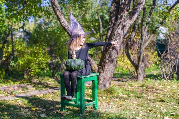Entzückendes kleines mädchen in halloween, welches kostüm spaß im freien hat