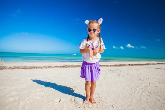 Entzückendes kleines mädchen in ostern-kostüm auf dem exotischen strand