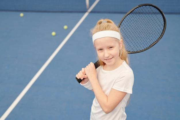 Entzückendes kleines mädchen in weißer activewear, das tennisschläger auf der rechten schulter hält, während es in stadionumgebung vor der kamera steht