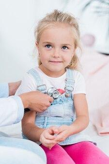 Entzückendes kleines mädchen mit blondem haar, das auf bett im medizinischen büro sitzt, während arzt sie mit stethoskop untersucht