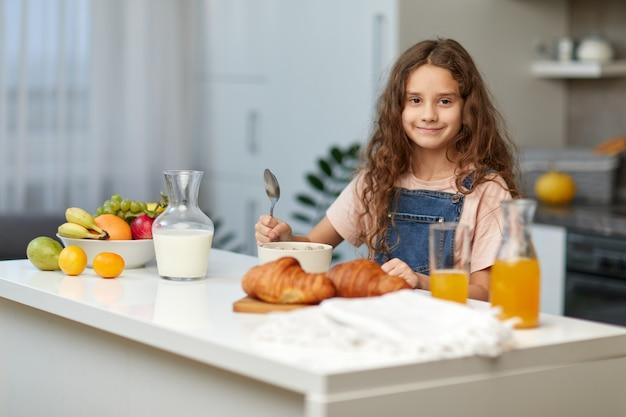 Entzückendes kleines mädchen mit dem lockigen haar, das gesundes frühstück des getreides in der küche isst und die kamera mit löffel in der hand betrachtet.