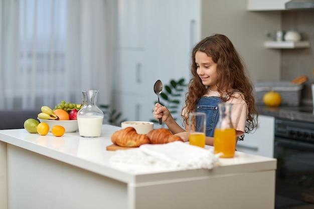 Entzückendes kleines mädchen mit dem lockigen haar, das gesundes frühstück des getreides in der küche isst.