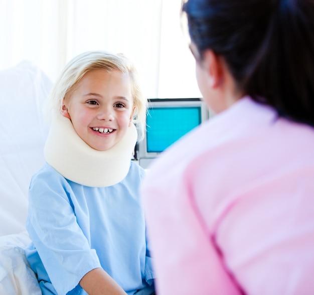 Entzückendes kleines mädchen mit einer stutzenklammer, die mit einer krankenschwester spricht