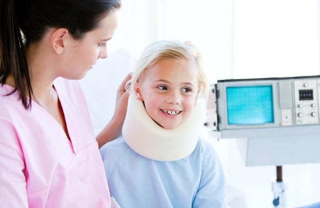 Entzückendes kleines mädchen mit einer stutzenklammer, die mit ihrer krankenschwester sitzt