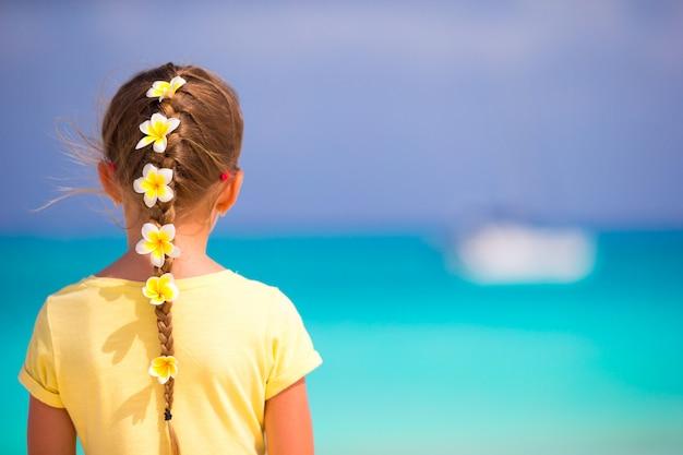 Entzückendes kleines mädchen mit frangipani blüht im haar auf strand