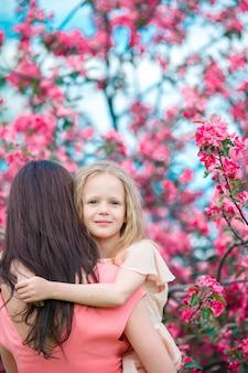 Entzückendes kleines mädchen mit junger mutter in blühendem kirschgarten am frühlingstag