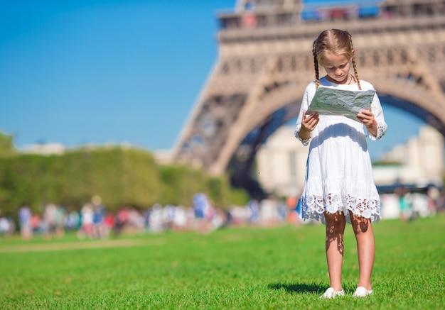 Entzückendes kleines mädchen mit karte von paris-hintergrund der eiffelturm