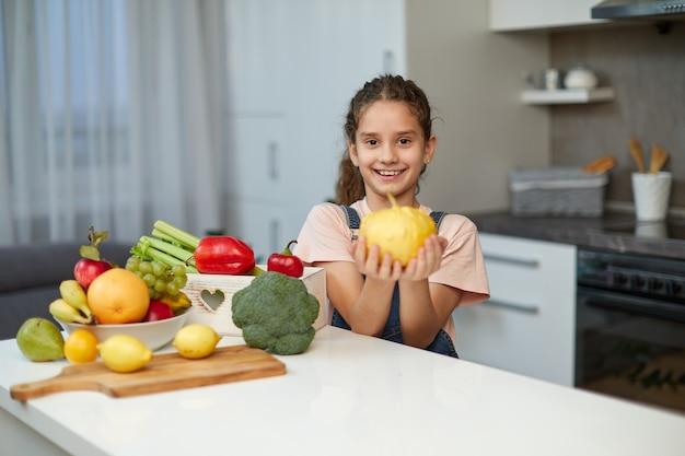 Entzückendes kleines mädchen mit lockigem haar, das einen gelben kürbis hält und am tisch in der küche sitzt.