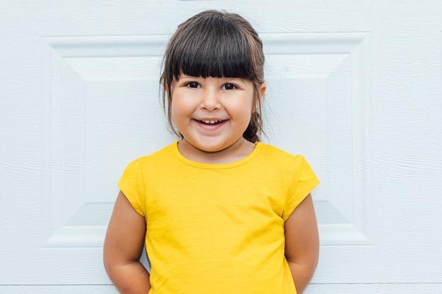 Entzückendes kleines mädchen mit schwarzen haaren, die ein gelbes hemd tragen, das gegen weißen hintergrund lehnt
