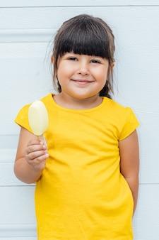 Entzückendes kleines mädchen mit schwarzen haaren, die eis essen, ein gelbes hemd tragend, das gegen weißen hintergrund lehnt