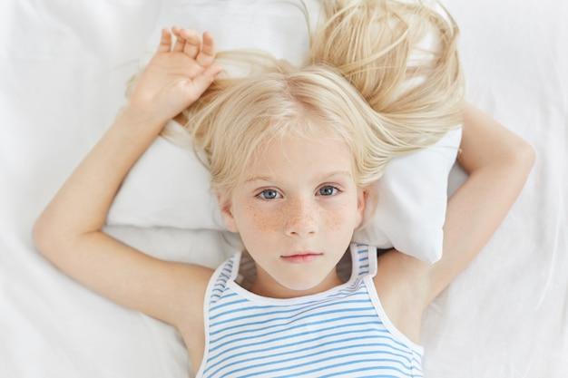 Entzückendes kleines mädchen mit sommersprossiger haut mit krankem blick, während auf weißem bett des krankenhauses liegend, mit ihren blauen bezaubernden augen schauend, ruhe haben wollen.
