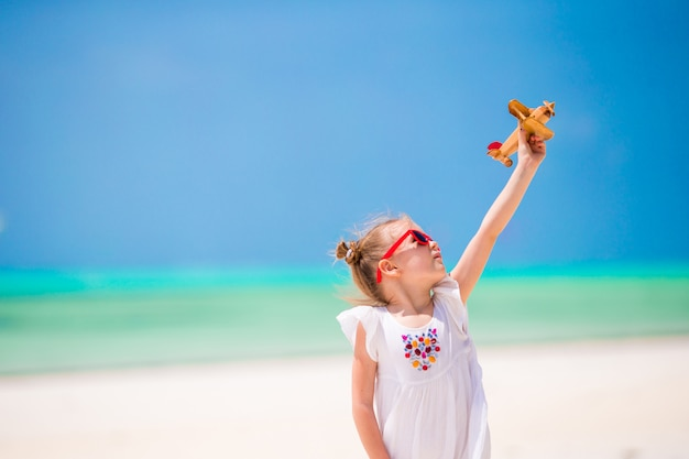 Entzückendes kleines mädchen mit spielzeugflugzeug in den händen auf weißem tropischem strand