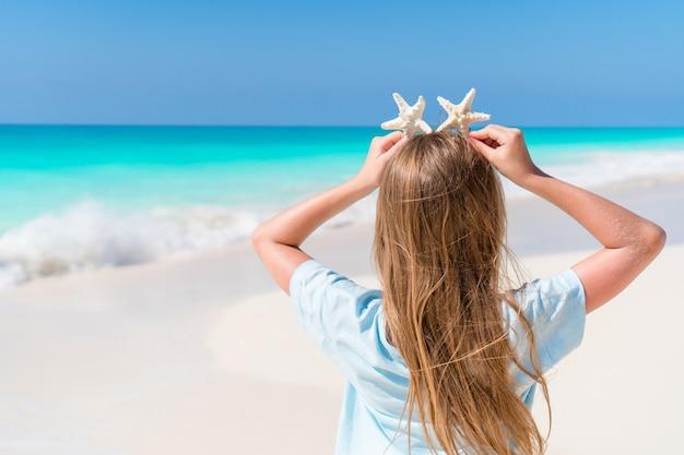 Entzückendes kleines mädchen mit starfish auf weißem leerem strand