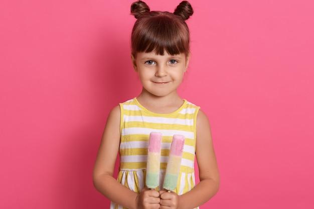 Entzückendes kleines mädchen mit zwei eiscreme in händen mit schüchternem ausdruck, weißes und gelbes kleid tragend, hat zwei haarbrötchen.