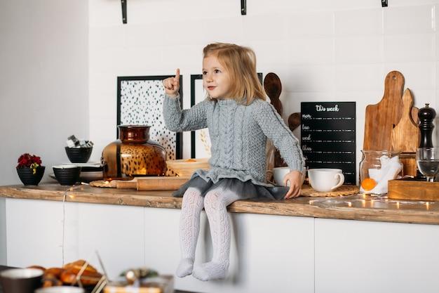 Entzückendes kleines mädchen sitzt auf küchentisch. kleines mädchen in der küche zu hause